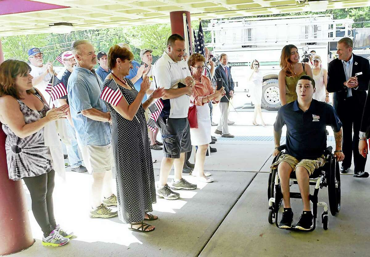 US Army Ranger SPC Sean Pesce, wounded in Afganstan and paralyzed from the waist down, with his girlfriend Mare Hassan of West Haven trailing behind with Bill Ivey, Executive Director of Homes For Our Troops, arrives at a community event at the Amity Regional Middle School in Bethany Saturday, August 13, 2016 welcoming him to Bethany after receiving the title to the Bethany property this week where his new home will be built by East Lyme-based builder Niantic Bay Group under the sponsorship of Homes For Our Troops. The single-level home will be mortgage free and specially adapted to Pesce's injuries to include widened doorways, lowered countertops, roll-under cook tops and sinks and other custom touches to give him full wheelchair accessibility.
