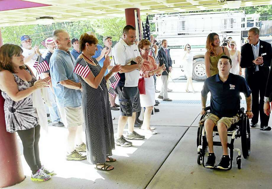 US Army Ranger SPC Sean Pesce, wounded in Afganstan and paralyzed from the waist down, with his girlfriend Mare Hassan of West Haven trailing behind with Bill Ivey, Executive Director of Homes For Our Troops, arrives at a community event at the Amity Regional Middle School in Bethany Saturday,  August 13, 2016 welcoming him to Bethany after receiving the title to the Bethany property this week where his new home will be built by East Lyme-based builder Niantic Bay Group under the sponsorship of Homes For Our Troops. The single-level  home will be mortgage free and specially adapted to Pesce's injuries to include widened doorways, lowered countertops, roll-under cook tops and sinks and other custom touches  to give him full wheelchair accessibility. Photo: Peter Hvizdak — New Haven Register   / ©2016 Peter Hvizdak