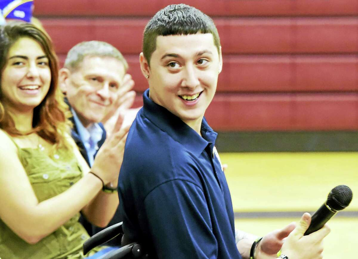 US Army Ranger SPC Sean Pesce, wounded in Afganstan and paralyzed from the waist down, right, with his girlfriend Mare Hassan of West Haven, left, and Bill Ivey, Executive Director of Homes For Our Troops, center, after speaking during a community event at the Amity Regional Middle School in Bethany Saturday, August 13, 2016 welcoming him to Bethany after receiving the title to the Bethany property this week where his new home will be built by East Lyme-based builder Niantic Bay Group under the sponsorship of Homes For Our Troops. The single-level home will be mortgage free and specially adapted to Pesce's injuries to include widened doorways, lowered countertops, roll-under cook tops and sinks and other custom touches to give him full wheelchair accessibility.