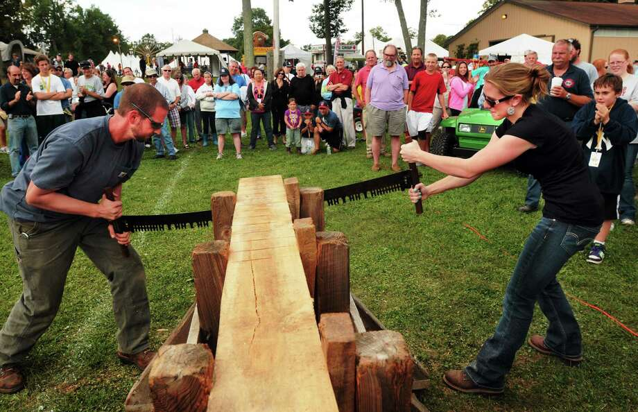 Ben Watts and his girlfriend Cara Shamansky, both of Bethany, compete to have the fastest time in the Jack-and-Jill two-person hand-saw contest at 2013's Orange Country Fair. Photo: Mara Lavitt — New Haven Register FILE PHOTO   / Mara Lavitt