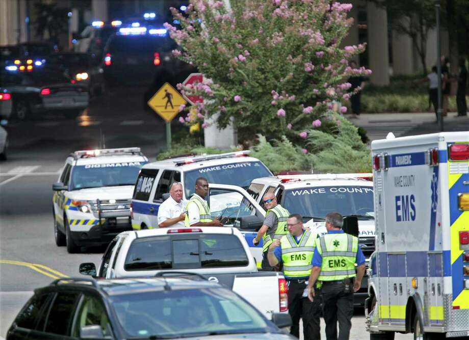 Wake EMS personnel stage their ambulances across Crabtree Creek on the back side of  Crabtree Valley Mall, Saturday, Aug. 13, 2016 after a reported shooting at the crowded mall in Raleigh, N.C. Law enforcement blue lights blink in the darkened background at the entrance to Belks at the popular Raleigh mall. Photo: Harry Lynch — The News & Observer Via AP / The News & Observer