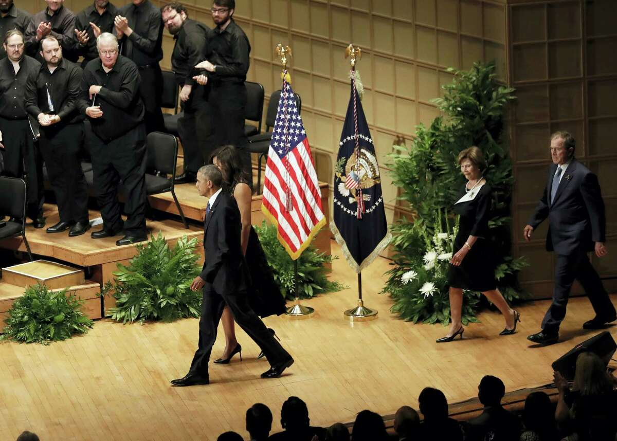 President Barack Obama and first lady Michelle Obama, followed by former President George W. Bush and Laura Bush, arrive for a memorial service at the Morton H. Meyerson Symphony Center, Tuesday, July 12, 2016, in Dallas. Five police officers were killed and several injured during a shooting in downtown Dallas last Thursday night.