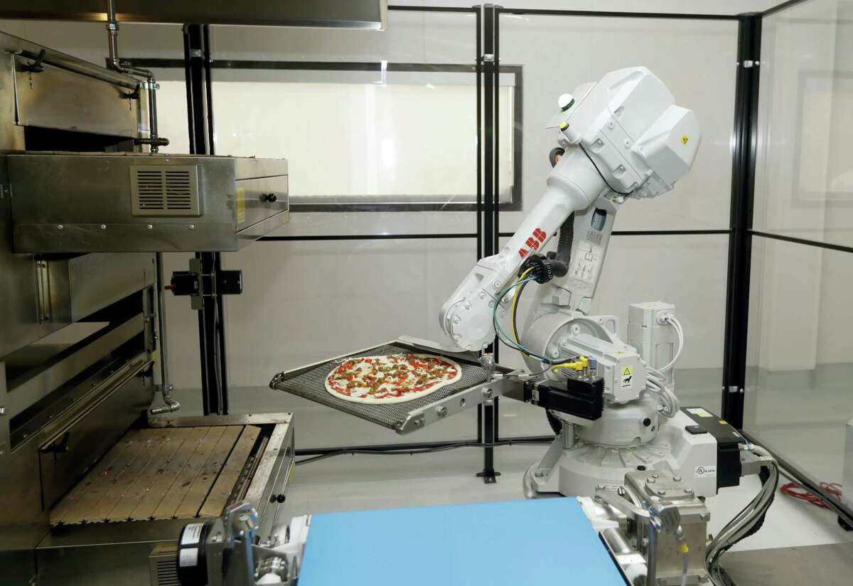 In this Monday, Aug. 29, 2016 photo, a robot places a pizza into an oven at Zume Pizza in Mountain View, Calif. The startup, which began delivery in April, is using intelligent machines to grab a slice of the multi-billion-dollar pizza delivery market. Zume is one of a growing number of food-tech firms seeking to disrupt the restaurant industry with software and robots that let them cut costs, speed production and improve worker safety.