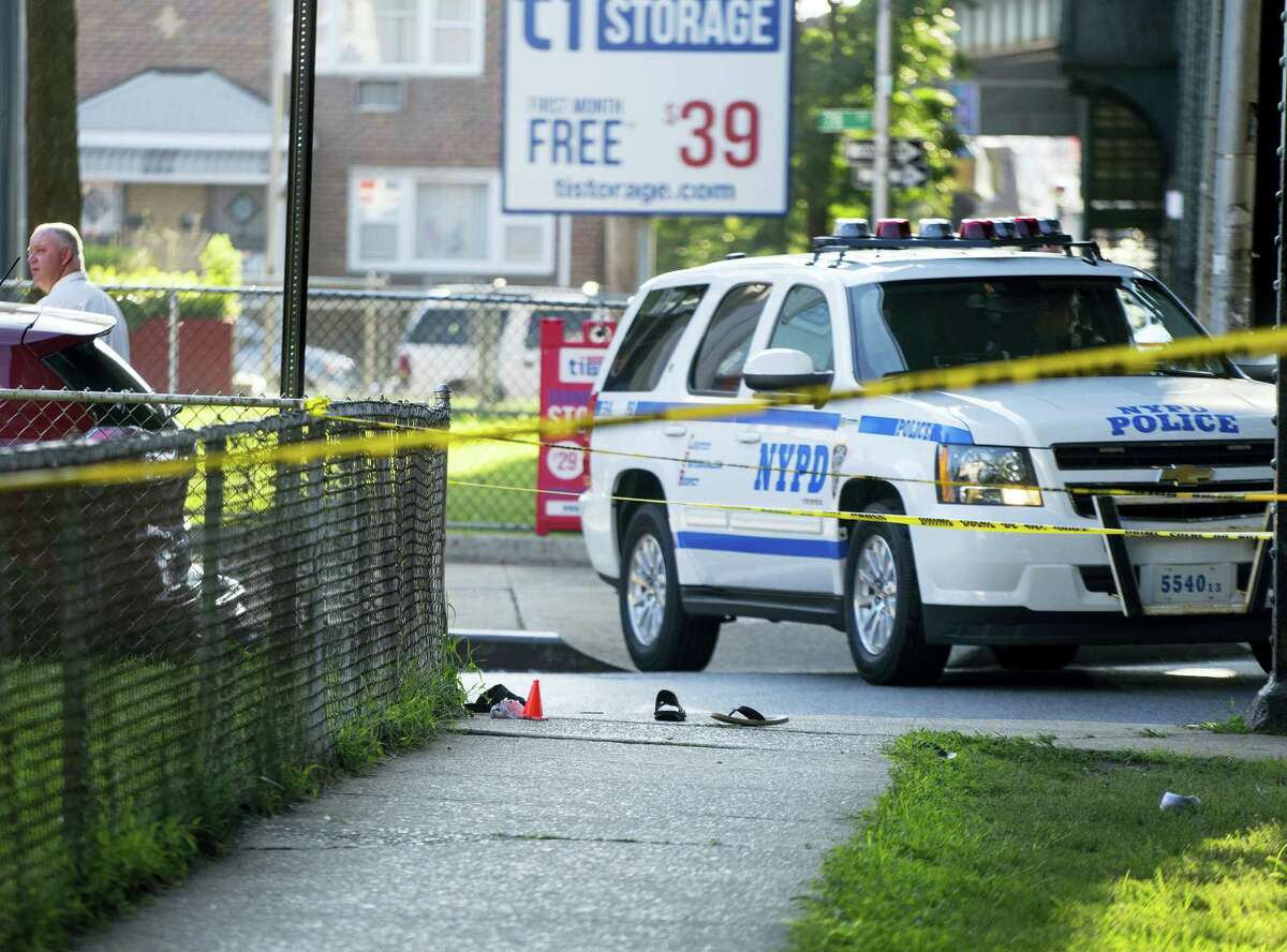 Sandals lay on a street corner at the crime scene, Saturday, Aug. 13, 2016, not far from the Al-Furqan Jame Masjid Mosque in the Ozone Park neighborhood of Queens, New York, where the leader of a New York City mosque has been fatally shot and an associate has been wounded in a brazen daylight attack.