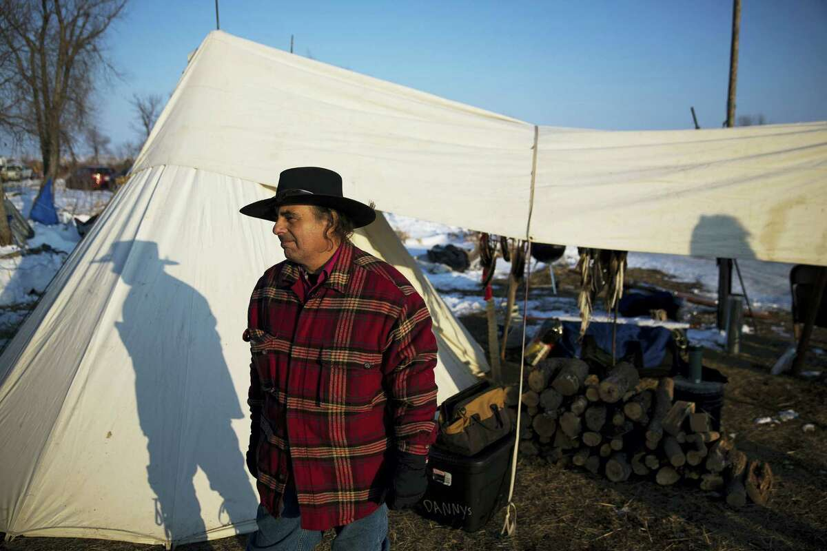"""Vietnam veteran Carlo Carlino, a Western Cherokee Native American from Ohio, stands outside his tent at the Oceti Sakowin camp where people have gathered to protest the Dakota Access oil pipeline in Cannon Ball, N.D. on Dec. 3, 2016. """"These are hereditary grounds. It comes down to where can we stay and not be pushed or moved,"""" said Carlino about why he came to the camp. """"So we become refugees in our own country."""""""