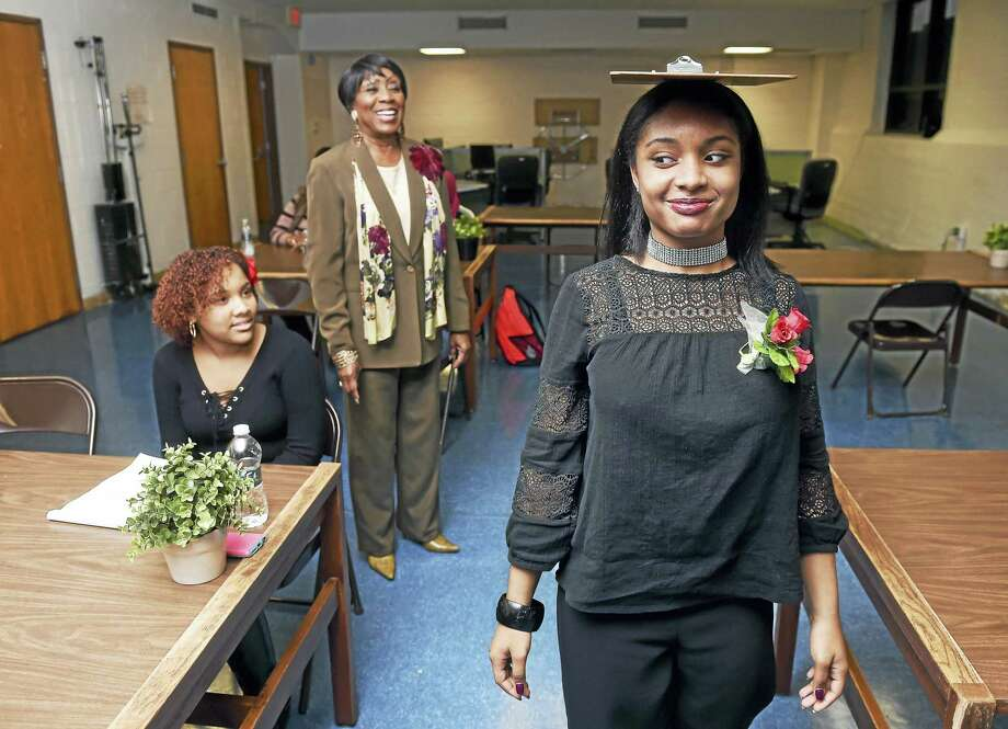 Left to right, Kennedi Cox, 17, and Carroll E. Brown, president of the West Haven Black Coalition, watch Faith Moody, 16, balance a board on her head to demonstrate good posture recently. Photo: Arnold Gold-New Haven Register
