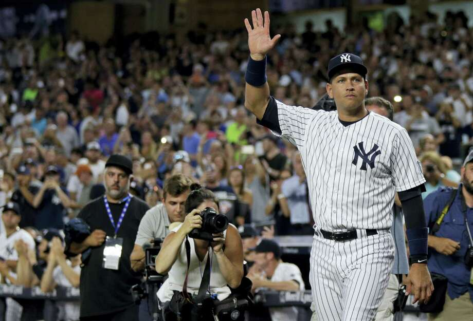 Alex Rodriguez acknowledges the crowd as he walks onto the field for a ceremony on Friday. Photo: Adam Hunger — The Associated Press   / FR110666 AP