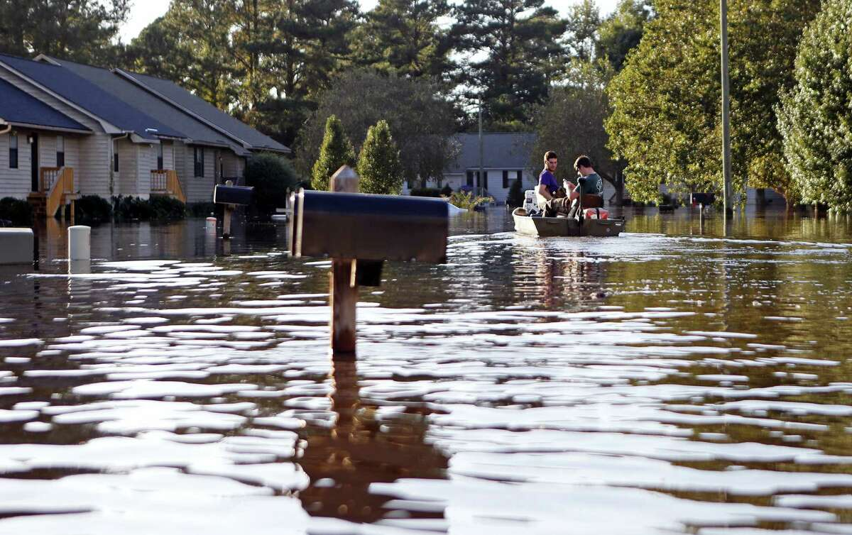 Kyle Hawley, right, and roommate Trey Wood, pilot their boat through the streets of their neighborhood, flooded by water associated with Hurricane Matthew, as they gather belongings from their home on Oct. 12, 2016 in Greenville, N.C.