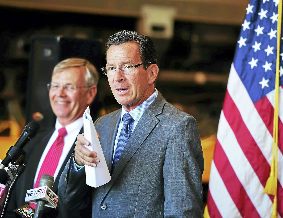 Gov. Dannel P. Malloy, right, and Connecticut Department of Transportation Commissioner James P. Redeker announce the purchase of 60 M8 rail cars for the New Haven Line operated by Metro-North Railroad, during a press conference Tuesday at the New Haven Rail Yard on Brewery Street.