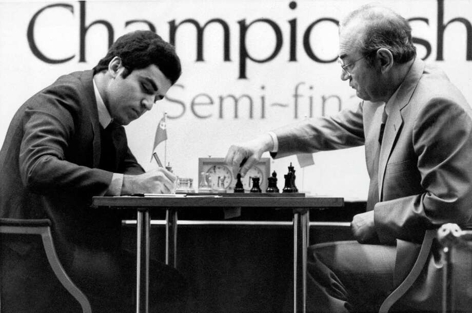 In this Nov. 25, 1983 file photo, Garry Kasparov, 20, left, the young Soviet number 2, makes notes as his opponent Russian exile Victor Korchnoi makes a move during the World Chess Championship semi-final in London. Chess grandmaster Victor Korchnoi, a prominent Soviet defector who saw his citizenship restored by Mikhail Gorbachev in the waning days of the USSR, has died on Monday, June 6, 2016. He was 85. The Russian chess federation says Korchnoi died in Switzerland, where he had lived for decades. (AP Photo/Taggart, file) Photo: AP / Copyright 2016 The Associated Press. All rights reserved. This material may not be published, broadcast, rewritten or redistribu