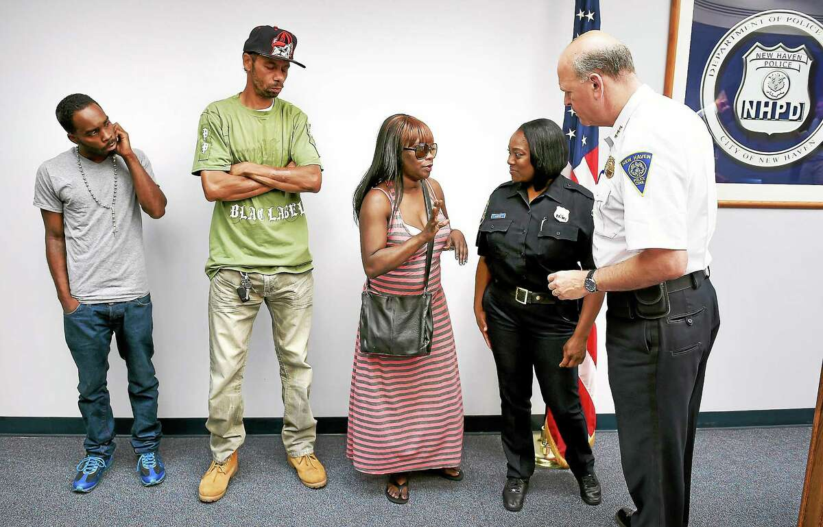 (Arnold Gold-New Haven Register) Left to right, Tyrese Jones' brother, William Jowers, and his parents, Jymeson and Felicia Jones, attend a press conference on 8/8/2014 at the New Haven Police Department announcing the arrest of Errol Godfrey-Hill in the shooting death of Tyrese Jones. At right is New Haven Police Chief Dean Esserman.