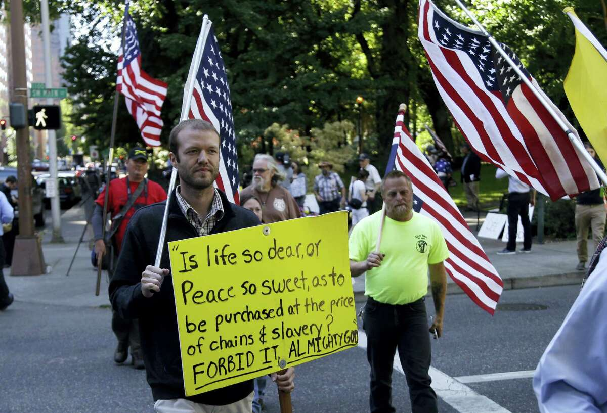 Protestors march outside the federal courthouse in Portland, Ore., Tuesday.