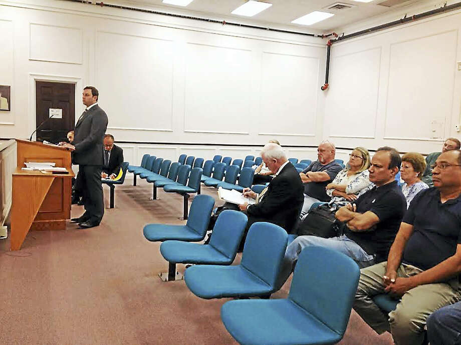 Attorney Evan Seeman of Robinson & Cole, who represents two holdout property owners in the project area for the proposed The Haven upscale outlet mall speaks to the West Haven Planning and Zoning Commission Tuesday night as his clients (second and third row) sit and listen. Behind Seeman are representatives of The Haven. Photo: MARK ZARETSKY — NEW HAVEN REGISTER