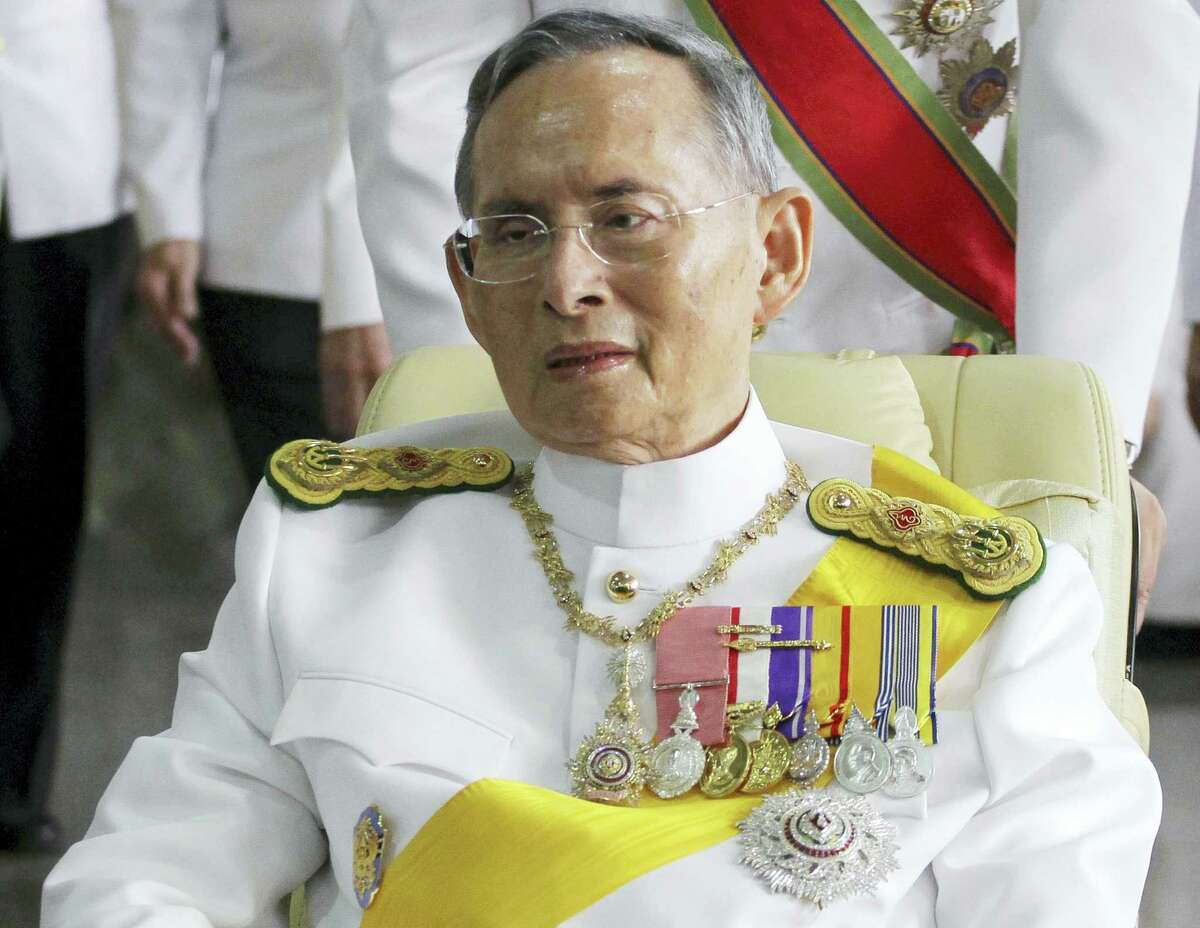 In this Dec. 5, 2011 photo, Thailand's King Bhumibol Adulyadej is pushed on a wheelchair while leaving Siriraj hospital for the Grand Palace for a ceremony celebrating his birthday in Bangkok. Hundreds of tearful Thais on Oct. 13, 2016 were continuing to offer flowers and chant prayers for King Bhumibol Adulyadej outside the Bangkok hospital where the world's longest-reigning monarch is being treated for multiple health problems.