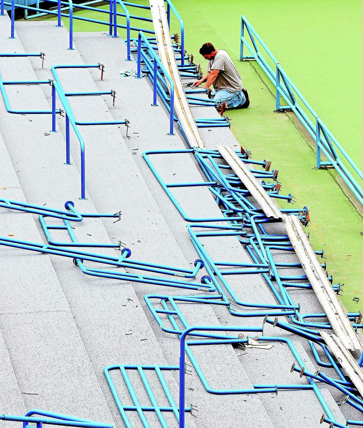 An installer works on railings in the Connecticut Tennis Center stadium court.