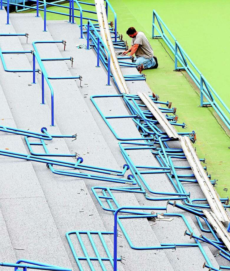 An installer works on railings in the Connecticut Tennis Center stadium court. Photo: File Photo