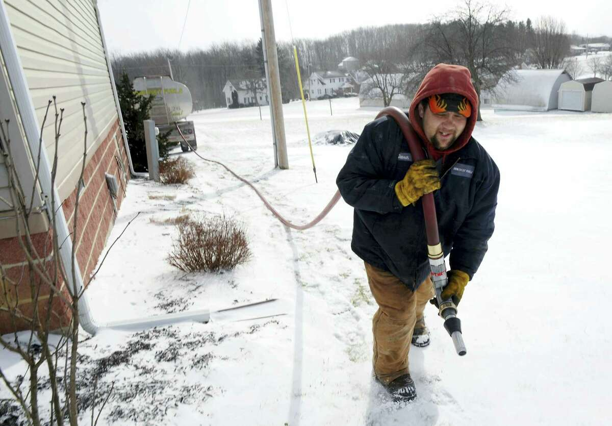 FILE - In this Jan. 7, 2014, file photo, Denver Walker, of Somerset Fuels, makes a heating oil delivery to a home in Jenner Crossroads, Pa. On Thursday, Oct. 13, 2016, the Energy Department said that household bills from October through March are likely to be higher for all four main heating fuels: natural gas, electricity, heating oil and propane. (John Rucosky/The Tribune-Democrat via AP, File)