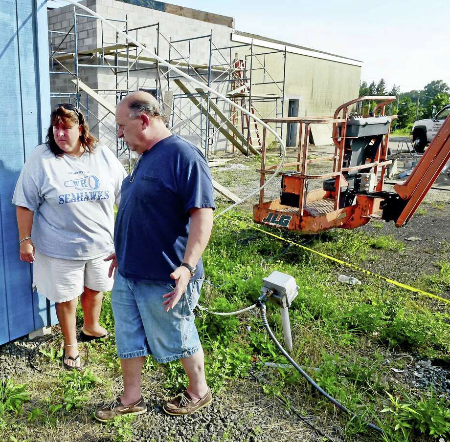 Cebi Waterfield, cheer coordinator for the West Haven Seahawk Football and Cheer program of the Ray Tellier Midget Football League, left,  with the uncompleted bathroom facility, right rear in photo, discusses the lack of electricity at theVeterans Memorial Park off Bull Hill Lane Monday evening, August 1, 2016  with a person familiar with the facility renovation  who wished to remain unidentified to the New Haven Register. West Haven Seahawks participants where at Veterans Memorial Park Monday evening to register for the upcoming season.  Over two years and 11-months ago, Gov. Dannel P. Malloy  stood in front of hundreds of players and parents from the West Haven Seahawks Pop Warner football and cheerleading programs to announce a $500,000 grant to improve the facilities at Veterans Memorial Park off Bull Hill Lane. The bathrooms are still not operational. Photo: Peter Hvizdak - New Haven Register   / ©2016 Peter Hvizdak
