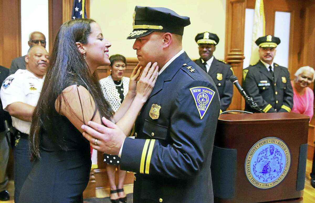 Leslie Reyes kisses her husband, New Haven Assistant Police Chief Otoniel Reyes, after pinning on his badge during his swearing-in and promotional ceremony at New Haven City Hall Thursday.