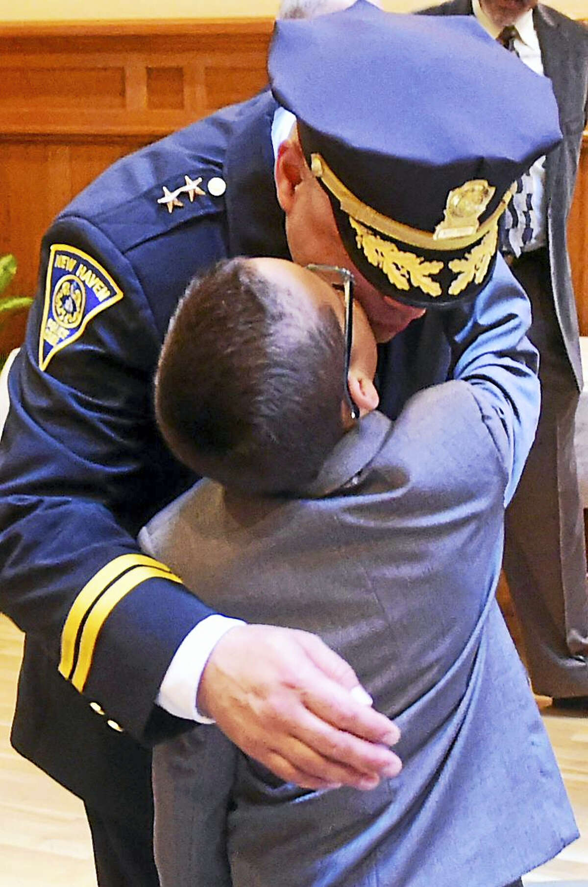 David Reyes,9, kisses his father, New Haven Assistant Police Chief Otoniel Reyes, before his swearing-in promotional ceremony Thursday.
