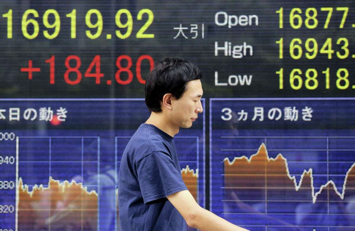 A man walks by an electronic stock board of a securities firm in Tokyo showing Japan's Nikkei 225 stock index that rose 184.80 points or 1.10 percent to close at 16,919.92, Friday. Asian shares rose Friday, tracking the rally in U.S. stocks that was driven by strong gains by energy companies and retailers. Rising oil prices also lifted sentiment. The retailers' earnings fueled optimism for the U.S. government's latest monthly tally of retail sales Friday.