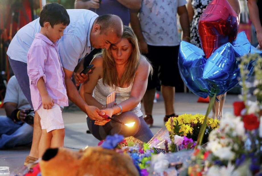 Well-wishers light candles at a makeshift memorial in honor of the slain Dallas police officers in front of police headquarters on Saturday. Photo: ASSOCIATED PRESS   / Copyright 2016 The Associated Press. All rights reserved. This material may not be published, broadcast, rewritten or redistribu