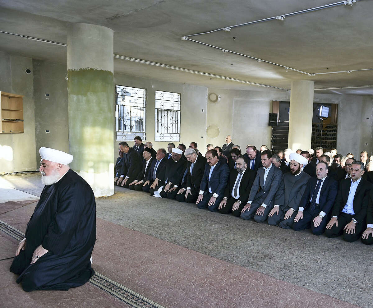 In this photo released on the official Facebook page of the Syrian Presidency, Syrian President Bashar Assad, fourth right, prays at the dawn Eid al-Adha prayers at the Saad ibn Muaaz Mosque in Daraya, a blockaded Damascus suburb, Syria on Sept. 12, 2016.