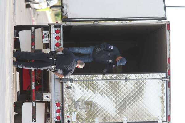Law enforcement personnel survey the scene where nine immigrants died in a tractor-trailer in San Antonio.