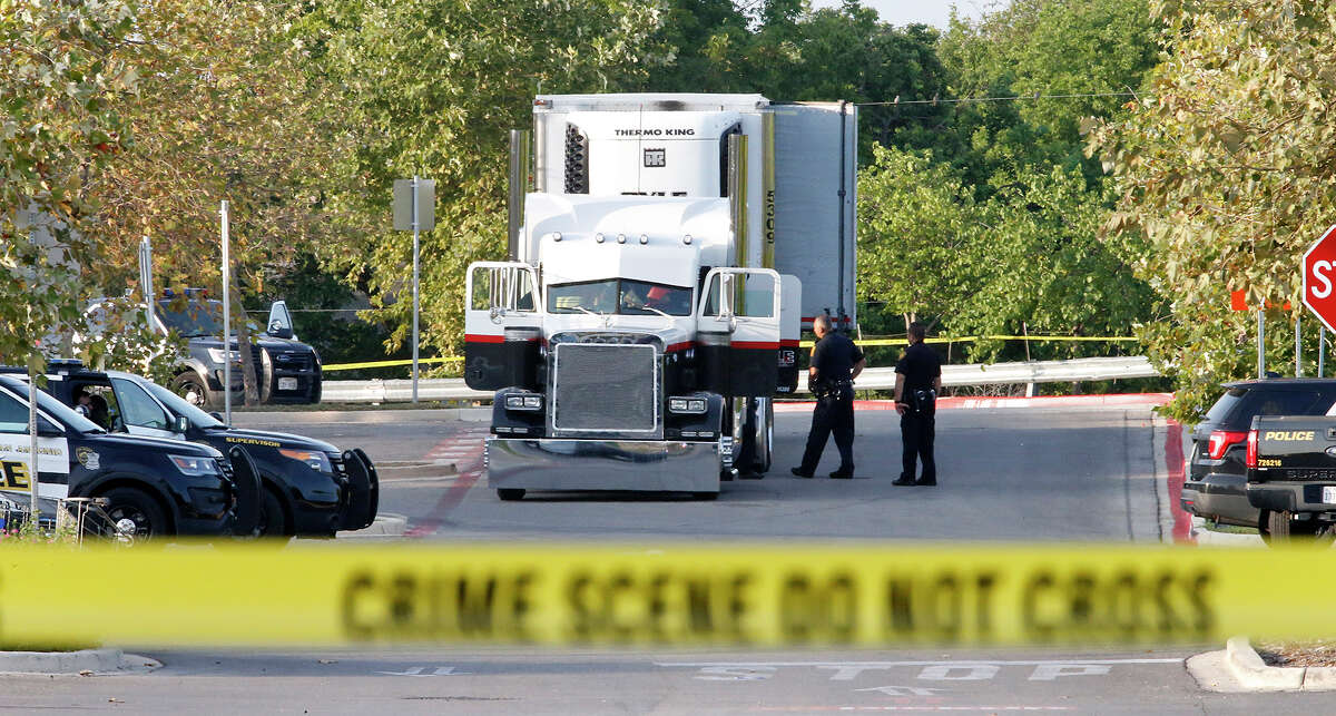 """San Antonio law enforcement officers investigate the scene Sunday. """"The truck was loaded with people,"""" Fire Chief Charls Hood said."""
