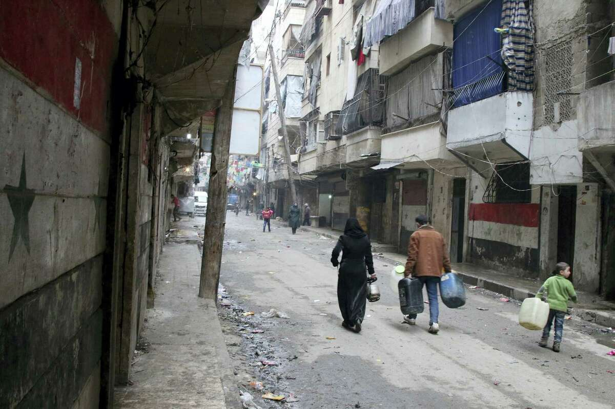 In this Feb. 11, 2016 photo, civilians walk with containers for fuel and water in Aleppo, Syria. Syrian rescue worker says three civilians, a mother and two children, died in a suspected chlorine gas attack on an opposition-held district in the city of Aleppo.