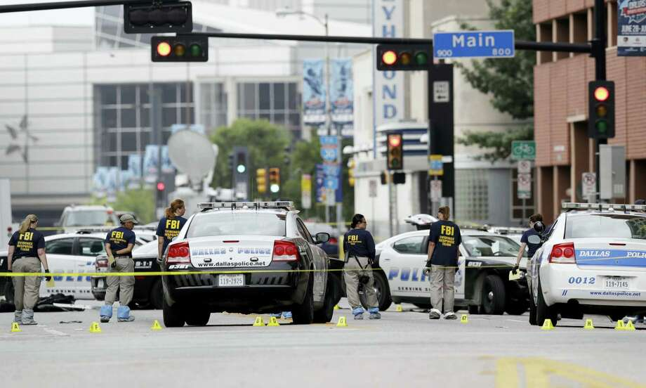 Investigators work in the area of downtown Dallas that remains an active crime scene on July 9, 2016. Micah Johnson, an Army veteran, opened fire on police officers in the heart of Dallas Thursday, July 7, 2016 as hundreds of people were gathered to protest two recent fatal police shootings of black men, Philando Castile and Alton Sterling. Photo: AP Photo/Eric Gay   / Copyright 2016 The Associated Press. All rights reserved. This material may not be published, broadcast, rewritten or redistribu