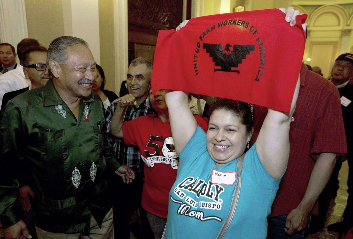 Maria Ceja, right, joined other farm workers in celebrating outside the Assembly Chambers after lawmakers approved a measure requiring farmworkers to receive overtime pay after working eight hours, at the Capitol, in Sacramento Calif. At left is Arturo Rodriguez, president of the United Farm Workers.