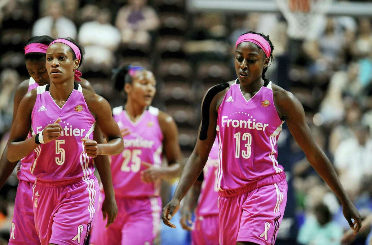 The Connecticut Sun's Jasmine Thomas, left, and Chiney Ogwumike walk off the court during a timeout in the second half Sunday.