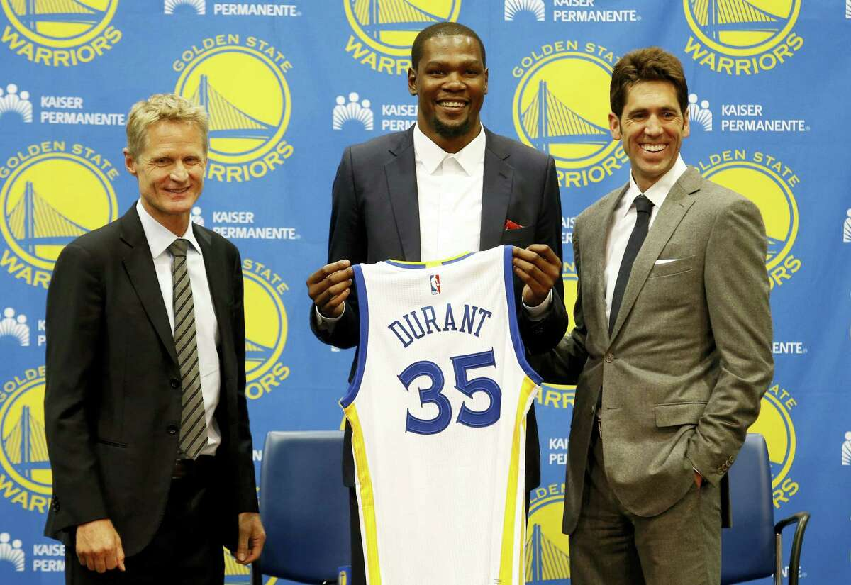 Kevin Durant, center, joins Golden State Warriors head coach Steve Kerr, left, and general manager Bob Myers during a news conference on Thursday in Oakland, Calif.