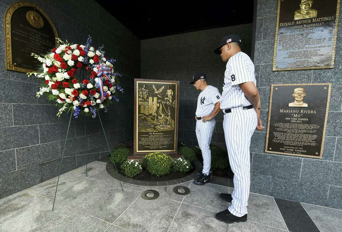 Yankees manager Joe Girardi, left and pitcher Dellin Betances view the September 11th memorial in Monument Park after placing a wreath next to it on Sunday.