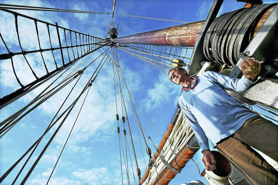 Evan, a senior deck hand who lives full-time on the Freedom Schooner Amistad, is seen beneath the hundred-foot mast, was back in the vessel's homeport at Long Wharf Pier in New Haven Wednesday. He would not provide his last name. Photo: Catherine Avalone — New Haven Register   / New Haven RegisterThe Middletown Press