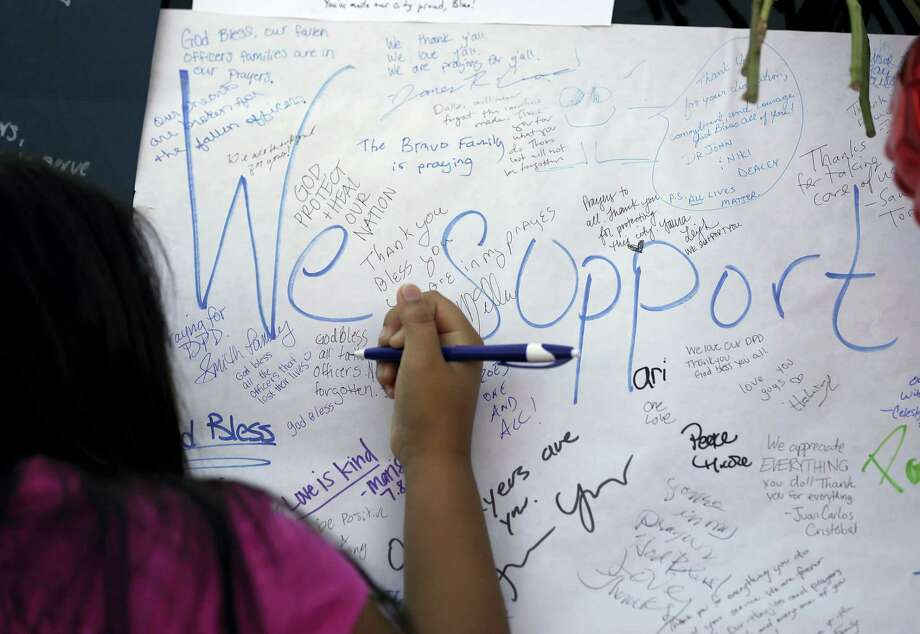 Jasmine Ruiz writes a note at a make-shift memorial in front of the Dallas police department Saturday. Photo: ASSOCIATED PRESS   / Copyright 2016 The Associated Press. All rights reserved. This material may not be published, broadcast, rewritten or redistribu
