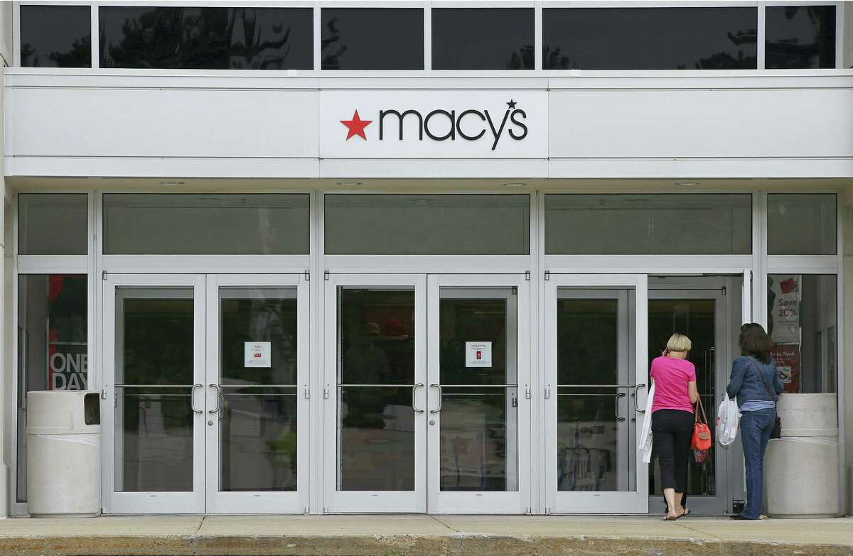 In this file photo, shoppers walk into a Macy's department store at the Hanover Mall in Hanover, Mass. Macy's reports financial results Thursday.