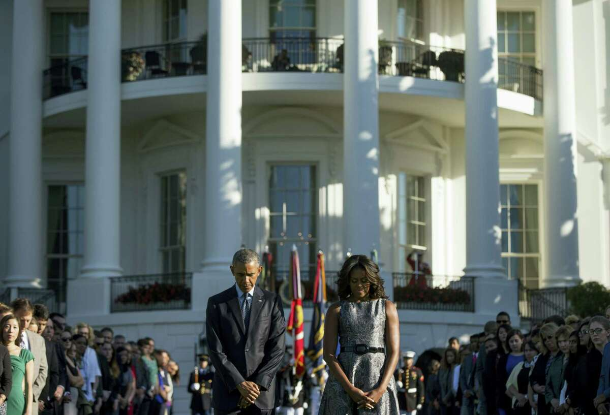 In this Sept. 11, 2015 photo, President Barack Obama, first lady Michelle Obama, and others, pause on the South Lawn of the White House in Washington as they observe a moment of silence to mark the 14th anniversary of the 9/11 attacks. President Barack Obama is joining the nation in remembering the nearly 3,000 people who died in the Sept. 11 attacks 15 years ago Sunday, Sept. 11, 2016.