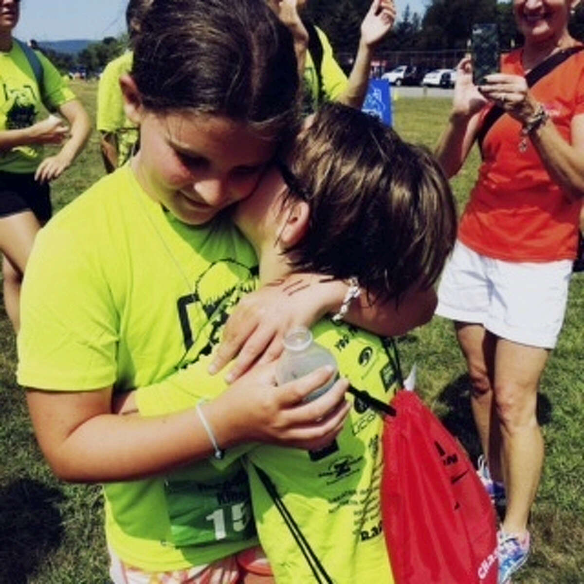 This undated photo provided by Heather Theriault shows Lily Rose Theriault, left and her friend Avary Gomez at the Race4Chase finish line. A triathlon program for children that was created by the family of a Sandy Hook shooting victim is getting some help from another Connecticut charity as it expands across the state and beyond. Bikes for Kids is providing 200 bicycles to be used in the Race4Chase Youth Triathlon program, which was created by the parents of 7-year-old Chase Kowalski. Lily Rose, went through the camp last year after going through some problems with bullying and self-esteem at school. It changed her life, her mother Heather Theriault said.