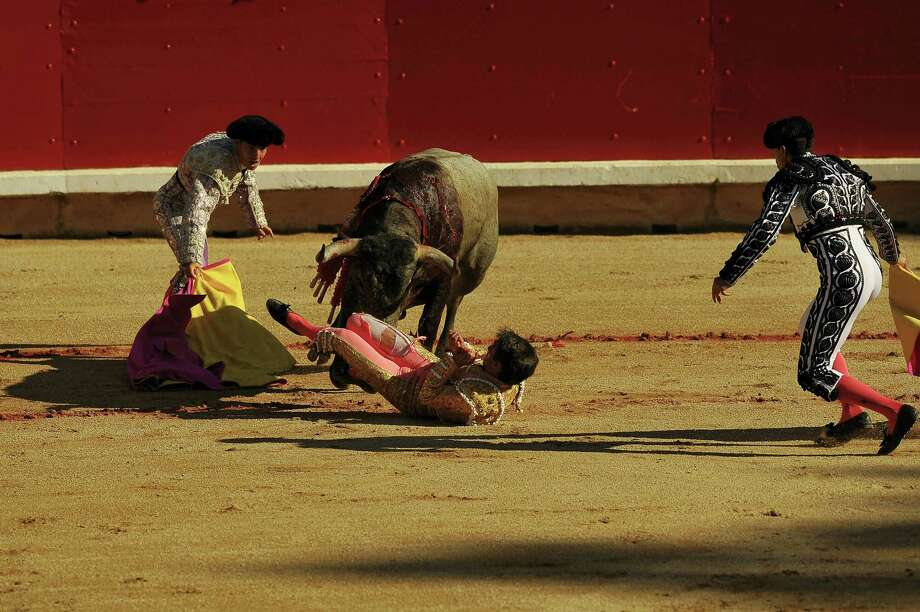 Spanish bullfighter, Francisco Marco, bottom right, is helped by the assistants after being gored by a bull from the Jose Escolar Gil ranch in the bullring during the San Fermin Festival, in Pamplona, northern Spain, Saturday, July 9, 2016. Revelers from around the world flock to Pamplona every year to take part in the eight days of the running of the bulls. Photo: AP Photo — Alvaro Barrientos / Copyright 2016 The Associated Press. All rights reserved. This material may not be published, broadcast, rewritten or redistribu
