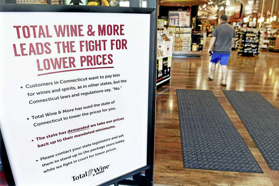 A sign displayed in the entrance to Total Wine & More in Milford Friday details the store's opposition to Connecticut's minimum pricing law for wines and spirits. Photo: Arnold Gold — New Haven Register