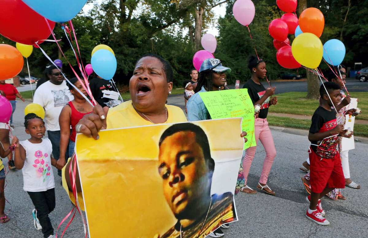 Sharon Cowan chants as she marches on the way to a candle light vigil on the spot where Mike Brown was killed on Aug. 9, 2016 in Ferguson, Mo. The demonstration marked two years since the unarmed black 18-year-old's fatal shooting by a white police officer.