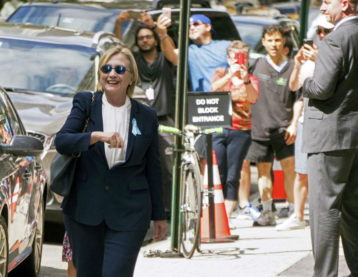 """Presidential candidate Hillary Clinton walks from from her daughter's apartment building Sunday after feeling """"overheated."""""""