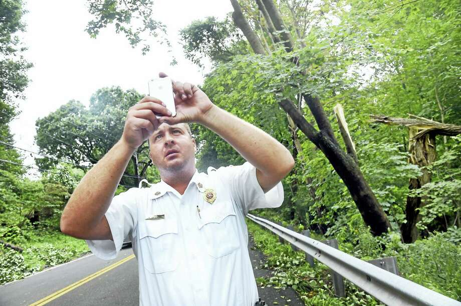 North Haven Police Chief Paul Januszewski takes photographs of storm damage on Middletown Avenue on Wednesday, Aug. 10, 2016. At right are some of the trees damaged in the storm. Photo: Arnold Gold — New Haven Register