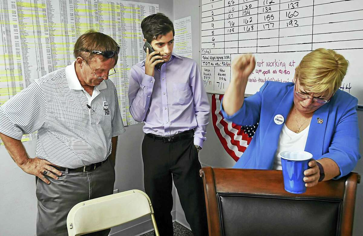 Kathy Hendricks, campaign manager pumps her fist, Tuesday, August 9, 2016, as Michael DiMassa gets a congratulatory phone call from State Rep. Matthew Lesser, of Middletown after DiMassa, a revenue clerk in the city's Tax Collector's Office won the Democratic primary for the 116th District state representative seat ousting fellow Democrat and 24-year veteran Louis P. Esposito Jr.. At left is James W. Morrissey, Democratic town chairman, at DiMassa's headquarters in West Haven. DiMassa defeated Esposito by 30 votes. (Catherine Avalone/New Haven Register)