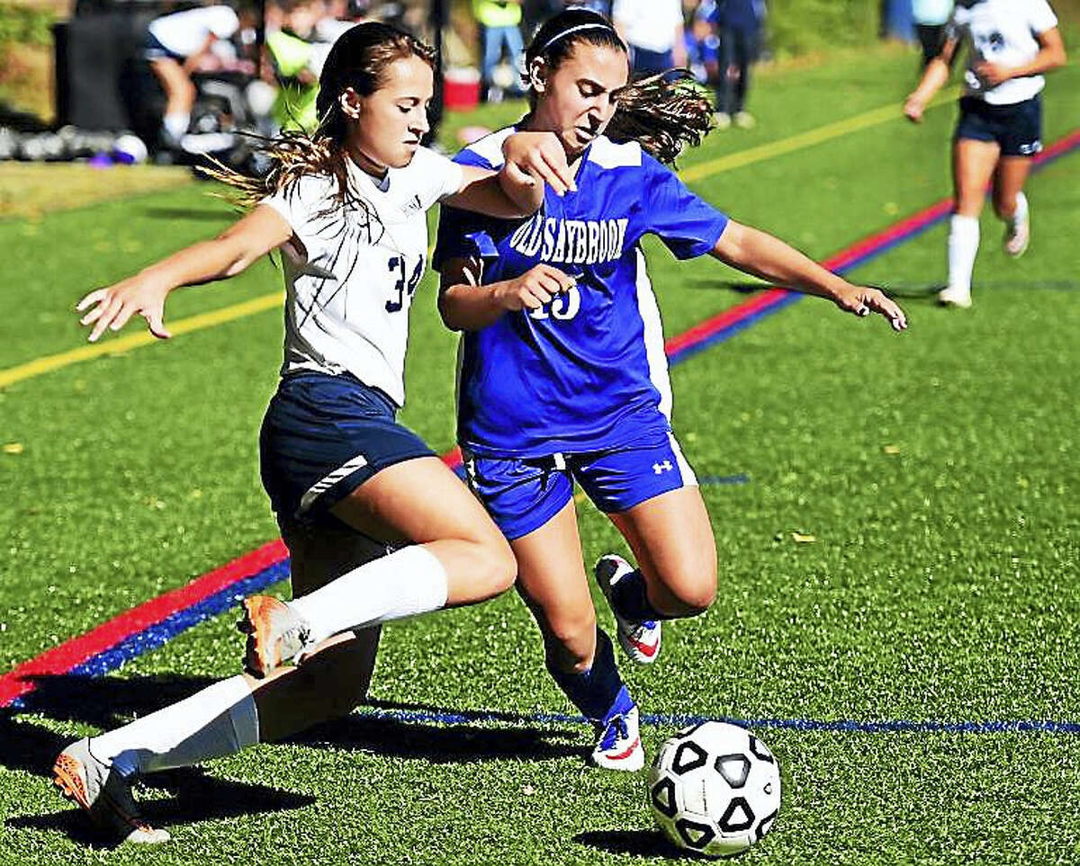 Kylee Clifton of Morgan, left, and Arianna Heonis of Old Saybrook fight for control of the ball during first-half girls soccer action Monday morning October 10, 2016, at the Indian River Complex in Clinton. Old Saybrook won 2-1.