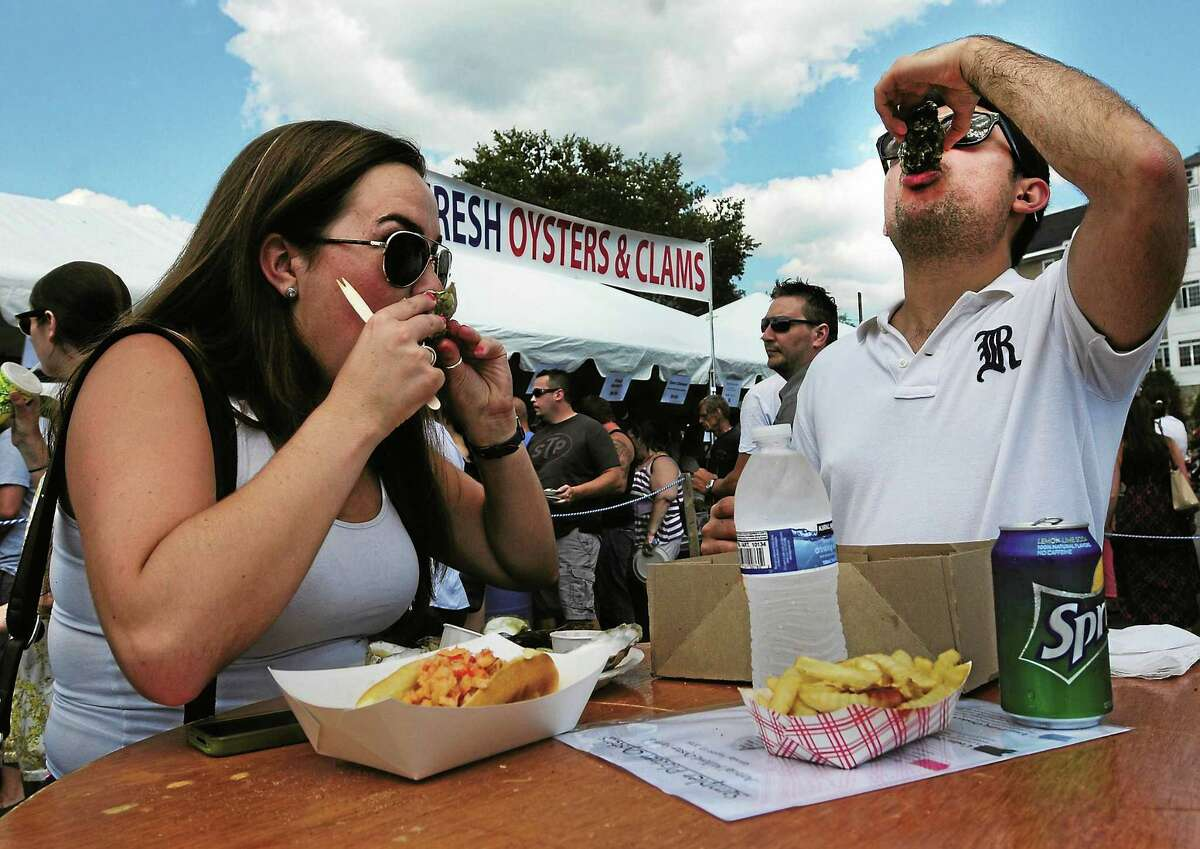 Christina Cool of New York City, left, with her friend Gustavo Colmenares of New Haven, partake in oysters together at the Milford Oyster Festival in 2013.