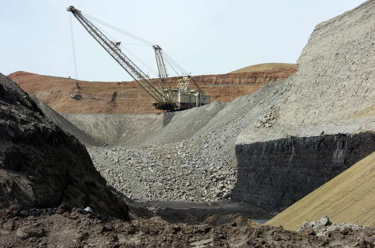 In this file photo, a dragline excavator moves rocks above a coal seam at the Spring Creek Mine in Decker, Mont.