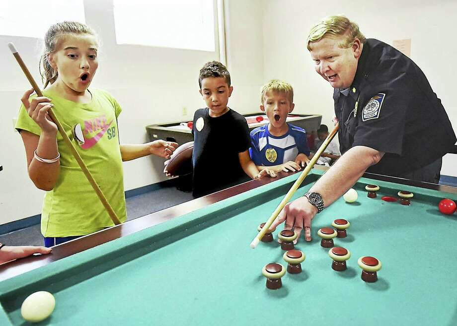 From left, Christiana Sansone, 10, Kamren Goins, 7, and Patrick Cooney, 8, watch Officer William King accidently sink Sansone's ball during a game of bumper pool at the Seymour Boys and Girls Club Wednesday. Photo: Catherine Avalone — New Haven Register   / New Haven RegisterThe Middletown Press